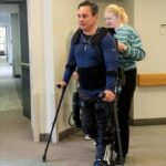 A research participant with spinal cord injury walks in the Ekso GT assisted by a physical therapist