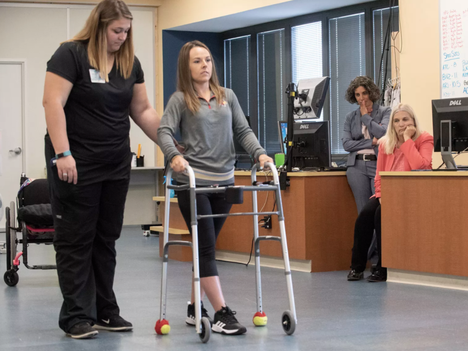Kelly Thomas walking with a walker, as study authors Claudia Angeli and Susan Harkema look on. Photo: University of Louisville
